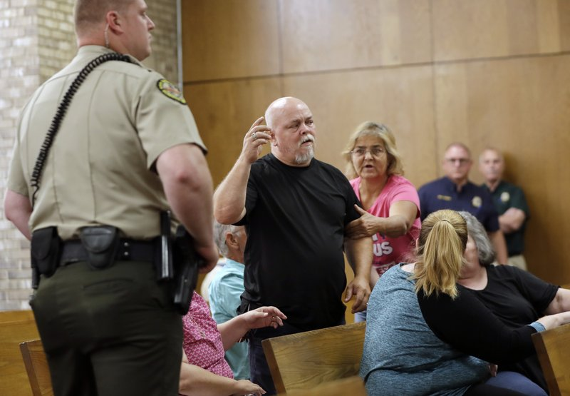 Steve McGlothlin, center, is escorted out of the courtroom after he yelled out as he heard testimony in the preliminary hearing for Michael Cummins Wednesday, May 29, 2019, in Gallatin, Tenn. Cummins faces multiple counts of first-degree murder in connection with the deaths of eight people in a nearby rural community in April. McGlothlin is a relative of some of the victims. (AP Photo/Mark Humphrey)