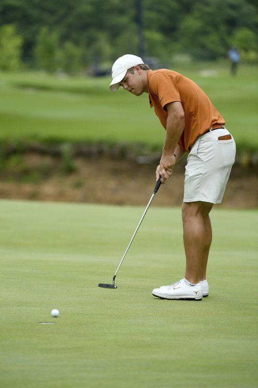 Texas's Pierceson Coody makes a putt on the 4th green during the final round against Stanford in the NCAA men's college golf tournament Wednesday, May 29, 2019, in Fayetteville, Ark. (AP Photo/Michael Woods)