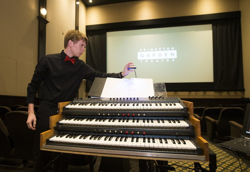 In this April 24, 2019 photo, Brett Miller adjusts the light on his organ prior to playing at Princeton Garden Theatre in Princeton, N.J., to the silent films