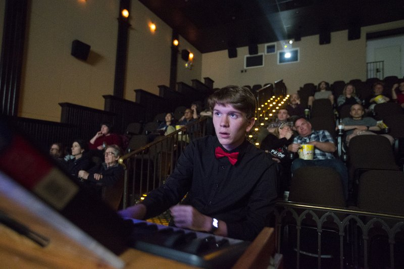 In this April 24, 2019 photo, Brett Miller plays in the glow of the movie screen at Princeton Garden Theatre  in Princeton, N.J., to the silent films