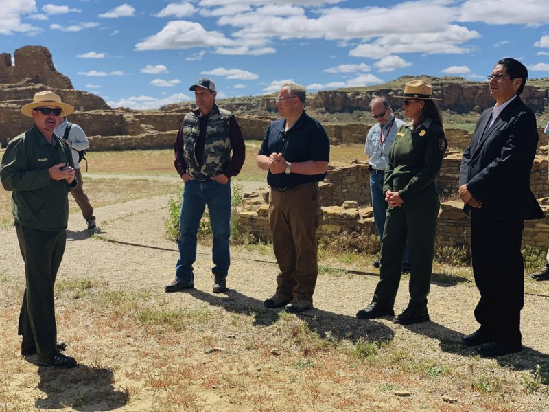 In this photo provided by the Navajo Nation, Interior Secretary David Bernhardt, center, tours Chaco Culture National Historical Park about 95 miles northeast of Gallup, New Mexico, on Tuesday, May 28, 2019. U.S. Sen. Martin Heinrich of New Mexico is at Bernhardt's right. Navajo Nation President Jonathan Nez is on his left. (Jared Touchin/Navajo Nation via AP)