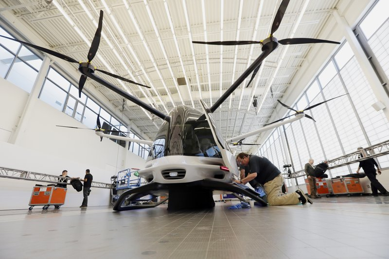 In this Tuesday, May 28, 2019, photo, workers prepare the Skai vehicle, developed by Alaka'i Technologies, for a special unveiling in Newbury Park, Calif. The transportation company is betting its hydrogen-powered electric flying vehicles will someday serve as taxis, cargo carriers and ambulances of the sky. (AP Photo/Marcio Jose Sanchez)