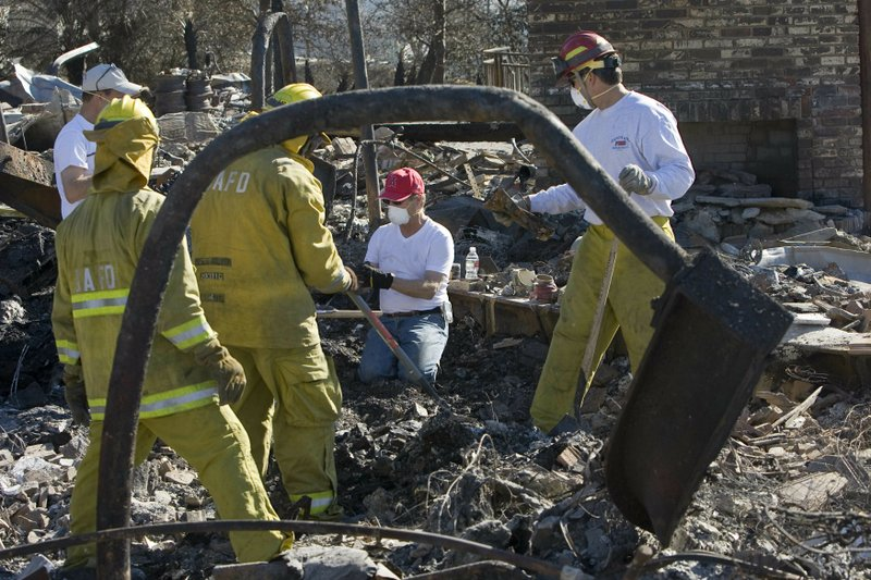FILE - In this Nov. 17, 2008 file photo, firefighters from Santa Ana Engine No. 4 help Lindy Lindholm, center, sift through the rubble of his burned out home in Yorba Linda, Calif. A group of public and private water systems in California have launched an advertising and lobbying campaign aimed at convincing lawmakers to shield them from having to pay damages caused by fires they did not start but failed to help put out. One lawsuit stemming from the 2008 fire forced the Yorba Linda Water District to pay $70 million to 12 homeowners. (AP Photo/Mark Avery, File)