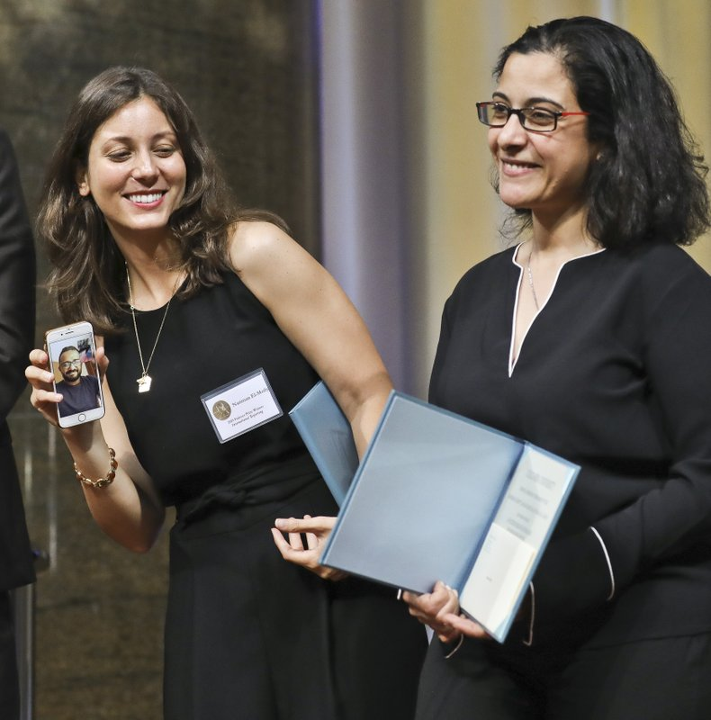 Associated Press Pulitzer Prize winners for International Reporting, Nariman El-Mofty, left, Maad al-Zikry, who joins by El-Mofty's cellphone video, and Maggie Michael pose with their prize certificates at an awards luncheon at Columbia University, Tuesday, May 28, 2019, in New York. AP has expressed disappointment that its Yemeni reporter, Maad al-Zikry, was unable to attend the ceremony to collect his Pulitzer Prize because he was not granted a U.S. visa. (AP Photo/Bebeto Matthews)