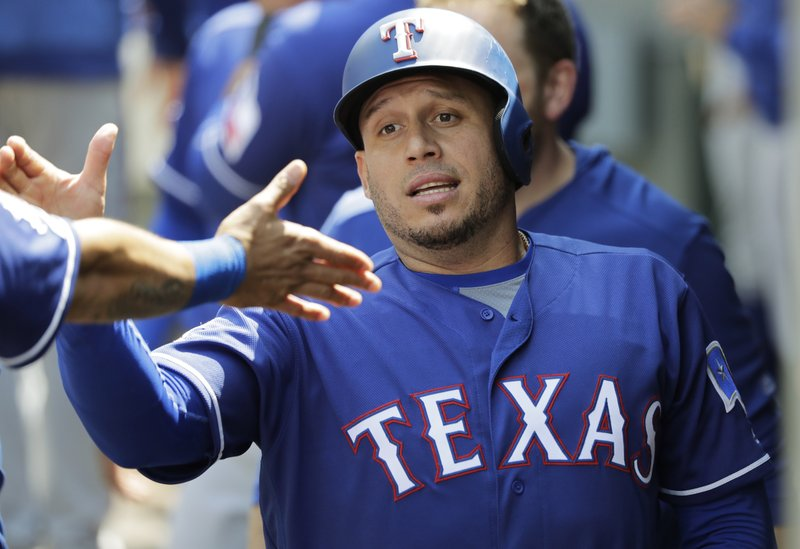 Texas Rangers' Asdrubal Cabrera is greeted in the dugout after he scored on a sacrifice fly hit by Ronald Guzman during the sixth inning of a baseball game against the Seattle Mariners, Wednesday, May 29, 2019, in Seattle. The Rangers won 8-7. (AP Photo/Ted S. Warren)