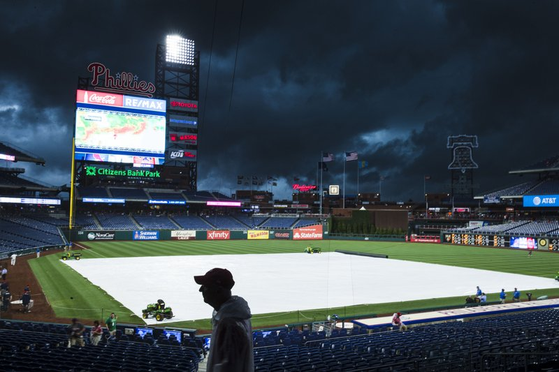 A tarp covers the field as a storm moves in ahead of baseball game between the Philadelphia Phillies and the St. Louis Cardinals, Wednesday, May 29, 2019, in Philadelphia. (AP Photo/Matt Rourke)