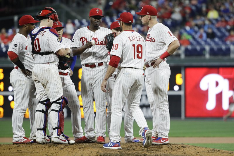 Philadelphia Phillies relief pitcher Edgar Garcia, center, hands the ball to manager Gabe Kapler (19) during the seventh inning of a baseball game against the St. Louis Cardinals, Tuesday, May 28, 2019, in Philadelphia. The Phillies won 4-3. (AP Photo/Matt Rourke)