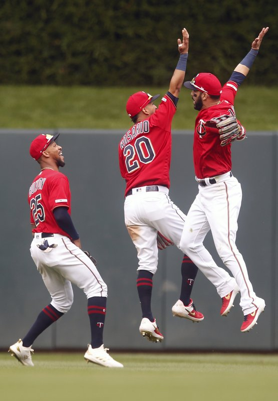 Minnesota Twins outfielders, from left, Byron Buxton, Eddie Rosario and Martin Gonzalez celebrate the Twins' 8-1 win over the Chicago White Sox after a baseball game Saturday May 25, 2019, in Minneapolis. (AP Photo/Jim Mone)