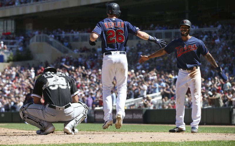 Minnesota Twins' Max Kepler, center, jumps in celebration with Martin Gonzalez, right, after Kepler's three-run home run off Chicago White Sox pitcher Josh Osich in the seventh inning of a baseball game Sunday, May 26, 2019, in Minneapolis. At left, looking down, is White Sox catcher Seby Zavala. The Twins won 7-0. (AP Photo/Jim Mone)
