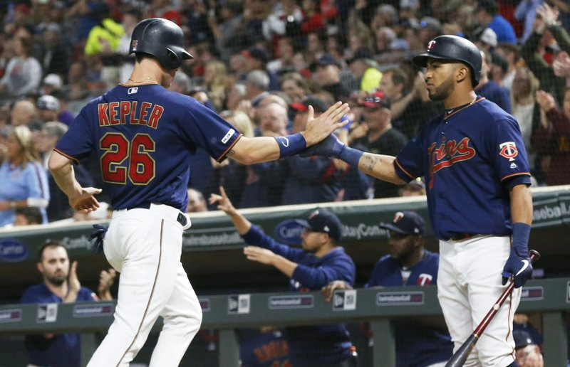 Minnesota Twins' Eddie Rosario, right, greets Max Kepler after he scored on a C.J. Cron double off Milwaukee Brewers pitcher Junior Guerra in the seventh inning of a baseball game, Tuesday, May 28, 2019, in Minneapolis. The Twins won 5-3. Both Kepler and Rosario had two RBIs each. (AP Photo/Jim Mone)