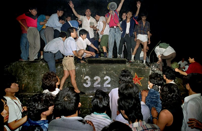 FILE - In this early June 4, 1989, file photo, civilians hold rocks as they stand on a government armored vehicle near Changan Boulevard in Beijing. Over seven weeks in 1989, student-led pro-democracy protests centered on Beijing's Tiananmen Square became China's greatest political upheaval since the end of the Cultural Revolution more than a decade earlier. (AP Photo/Jeff Widener, File)