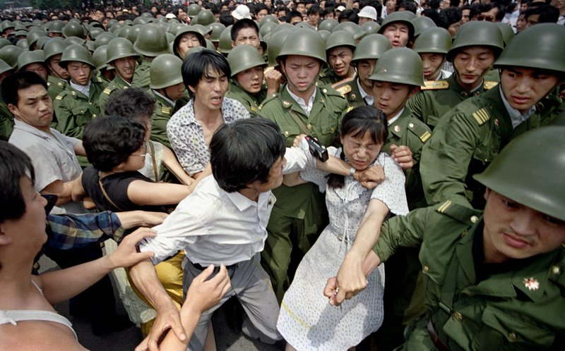 FILE - In this June 3, 1989 file photo, a young woman is caught between civilians and Chinese soldiers, who were trying to remove her from an assembly near the Great Hall of the People in Beijing. Over seven weeks in 1989, the student-led pro-democracy protests centered on Beijing's Tiananmen Square became China's greatest political upheaval since the end of the decade-long Cultural Revolution more than a decade earlier.(AP Photo/Jeff Widener, File)