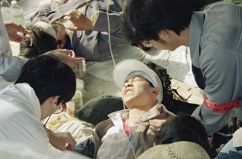 FILE - In this May 17, 1989 file photo, a striking Beijing University student is given first aid by medics at a field hospital in Tiananmen Square at Beijing, the fourth day of their hunger strike for democracy. Over seven weeks in 1989, the student-led pro-democracy protests centered on Beijing's Tiananmen Square became China's greatest political upheaval since the end of the decade-long Cultural Revolution more than a decade earlier.(AP Photo/Sadayuki Mikami, File)
