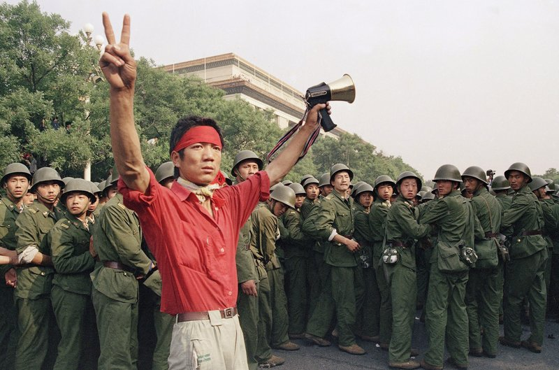 FILE - In this Saturday, June 3, 1989 file photo, a student pro-democracy protester flashes victory signs to the crowd as People's Liberation Army troops withdraw on the west side of the Great Hall of the People near Tiananmen Square in Beijing. Over seven weeks in 1989, the student-led pro-democracy protests centered on Beijing's Tiananmen Square became China's greatest political upheaval since the end of the decade-long Cultural Revolution more than a decade earlier.(AP Photo/Mark Avery, File)