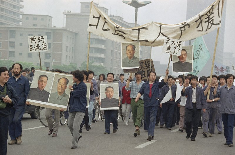 FILE - In this May 18, 1989 file photo, pro Democracy demonstrators carry portraits of former Chinese rulers Mao Tse-Tung and Chou En-Lai as they march to join student strikers at Tiananmen Square, Beijing, China. Over seven weeks in 1989, the student-led pro-democracy protests centered on Beijing's Tiananmen Square became China's greatest political upheaval since the end of the decade-long Cultural Revolution more than a decade earlier. (AP Photo/Sadayuki Mikami, File)