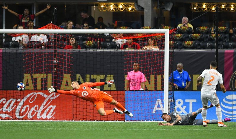 Minnesota United goalkeeper Vito Mannone dives as Atlanta United defender Franco Escobar (2) gets a shot past him to score during the first half of an MLS soccer match Wednesday, May 29, 2019, in Atlanta. (AP Photo/John Amis)