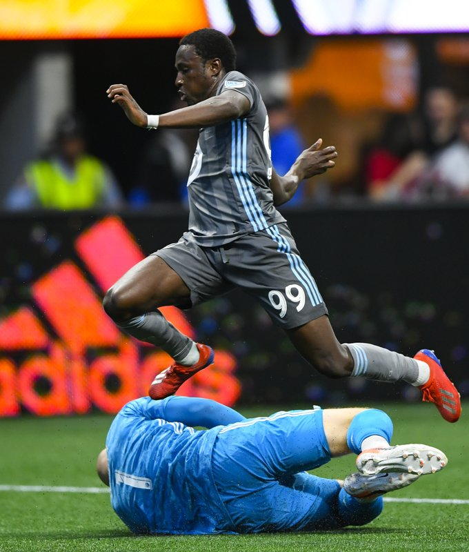 Atlanta United goalkeeper Brad Guzan makes a save as Minnesota United forward Abu Danladi (99) leaps over him after a shot during the first half of an MLS soccer match Wednesday, May 29, 2019, in Atlanta. (AP Photo/John Amis)