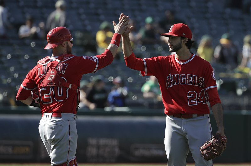 Los Angeles Angels catcher Jonathan Lucroy (20) celebrates with relief pitcher Noe Ramirez (24) after defeating the Oakland Athletics in 11 innings in a baseball game in Oakland, Calif., Wednesday, May 29, 2019. (AP Photo/Jeff Chiu)