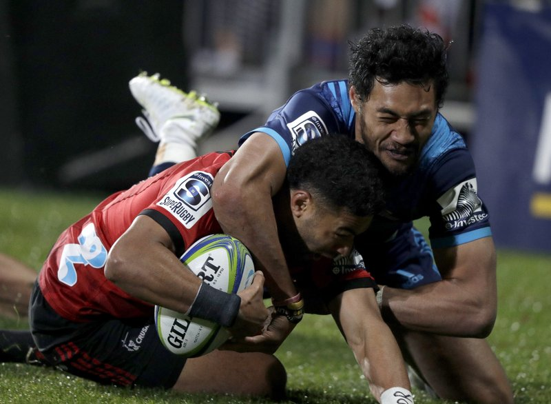 Crusaders Richie Mo'unga is tackled by Blues Melani Nanai, right, as he attempts to score a try during their Super Rugby match in Christchurch, New Zealand, Saturday, May 25, 2019. (AP Photo/Mark Baker)