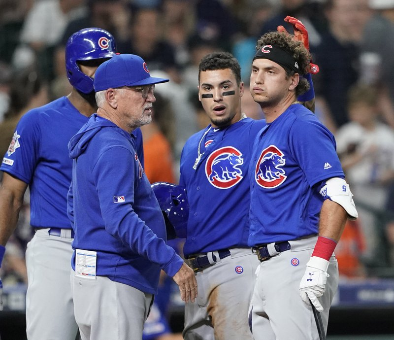 Chicago Cubs' Albert Almora Jr., right, reacts after hitting a foul ball into the stands as, from left to right, Jason Heyward, manager Joe Maddon and Javier Baez talk with him during the fourth inning of a baseball game against the Houston Astro Wednesday, May 29, 2019, in Houston. (AP Photo/David J. Phillip)