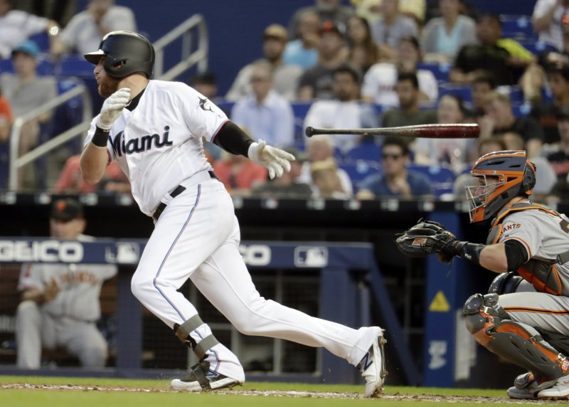 Miami Marlins' Austin Dean tosses his bat after hitting a single during the third inning of the team's baseball game against the San Francisco Giants, Wednesday, May 29, 2019, in Miami. At right is Giants catcher Buster Posey. (AP Photo/Lynne Sladky)