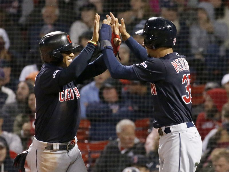 Cleveland Indians' Francisco Lindor, left, and Oscar Mercado celebrate after scoring on a double by Carlos Santana during the seventh inning of the team's baseball game against the Boston Red Sox, Wednesday, May 29, 2019, in Boston. (AP Photo/Mary Schwalm)