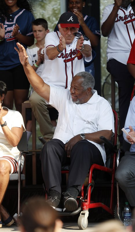Former Atlanta Braves outfielder Hank Arron waves as former pitcher Phil Niekro applauds during a ceremony to announce that Atlanta will host baseball's 2021 All-Star Game, Wednesday, May 29, 2019, in Atlanta. (AP Photo/John Bazemore)
