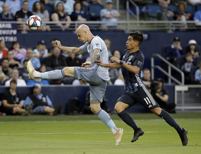 Sporting Kansas City midfielder Yohan Croizet, left, kicks the ball away from LA Galaxy midfielder Favio Alvarez during the first half of an MLS soccer match Wednesday, May 29, 2019, in Kansas City, Kan. (AP Photo/Charlie Riedel)