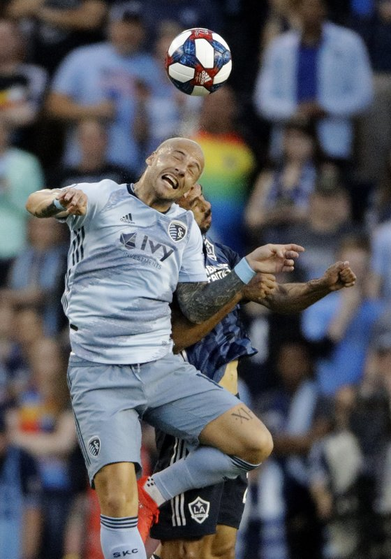 Sporting Kansas City midfielder Yohan Croizet, front, beats LA Galaxy defender Giancarlo Gonzalez to the ball during the first half of an MLS soccer match Wednesday, May 29, 2019, in Kansas City, Kan. (AP Photo/Charlie Riedel)