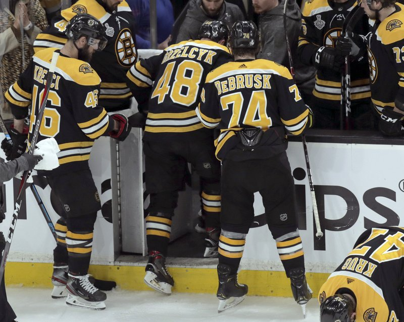 Boston Bruins' Matt Grzelcyk (48) heads to the dressing room after an injury during the first period in Game 2 of the NHL hockey Stanley Cup Final against the St. Louis Blues, Wednesday, May 29, 2019, in Boston. (AP Photo/Charles Krupa)