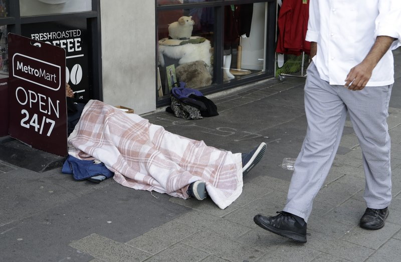A man sleeps on the street in the central business district of Christchurch, New Zealand, Thursday, May 30, 2019. The liberal-led government on Thursday unveiled the country's first so-called well-being budget, which aims to measure social outcomes like health and the environment alongside traditional metrics such as economic growth. (AP Photo/Mark Baker)