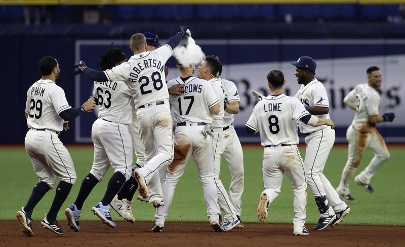 Teammates mob Tampa Bay Rays' Willy Adames after he drove in the winning run off Blue Jays relief pitcher Justin Shafer during the 11th inning of a baseball game Wednesday, May 29, 2019, in St. Petersburg, Fla. The Rays won 4-3. (AP Photo/Chris O'Meara)