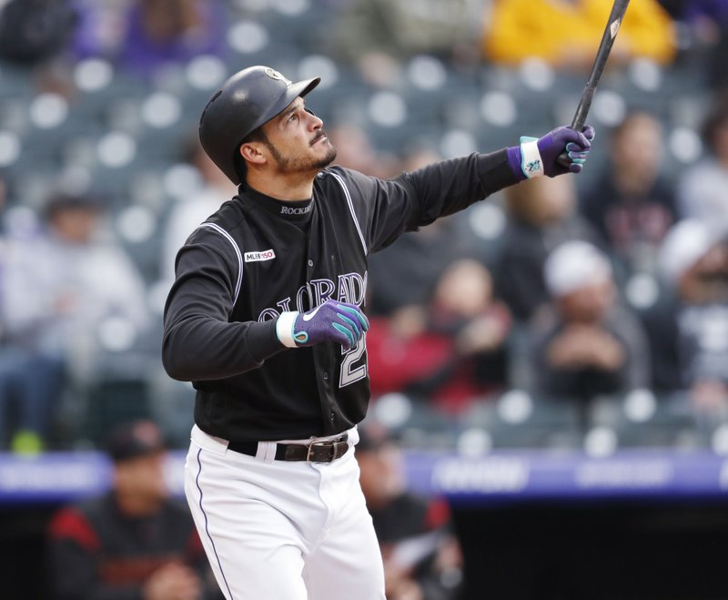 Colorado Rockies' Nolan Arenado follows the flight of his sacrifice fly off Arizona Diamondbacks starting pitcher Robbie Ray in the first inning of a baseball game Wednesday, May 29, 2019, in Denver. (AP Photo/David Zalubowski)