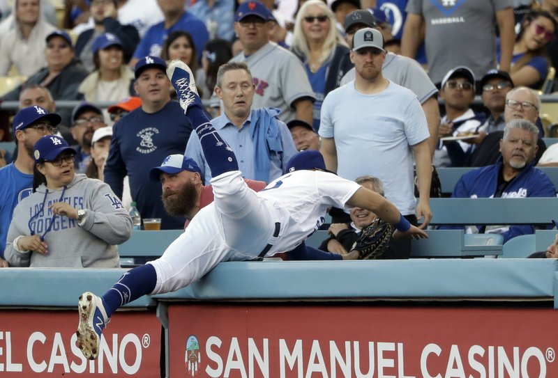 Los Angeles Dodgers first baseman Matt Beaty leaps into the stands chasing a foul ball from New York Mets' Amed Rosario during the first inning of a baseball game Wednesday, May 29, 2019, in Los Angeles. Beaty did not make a catch on the play. (AP Photo/Marcio Jose Sanchez)