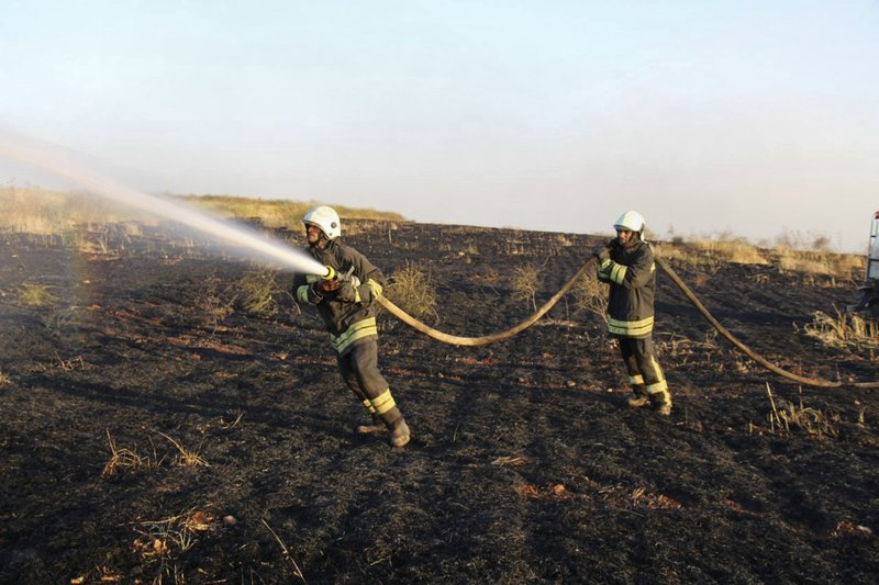 This Tuesday, May 28, 2019 photo, provided by the Syrian Civil Defense White Helmets, which has been authenticated based on its contents and other AP reporting, shows Syrian White Helmet civil defense workers trying to extinguish a fire in a field of crops, in Kfar Ain, the northwestern province of Idlib, Syria. Crop fires in parts of Syria and Iraq have been blamed on defeated Islamic State group militants in the east seeking to avenge the group's losses, and on Syrian government forces in the west battling to rout other armed groups there. (Syrian Civil Defense White Helmets via AP)