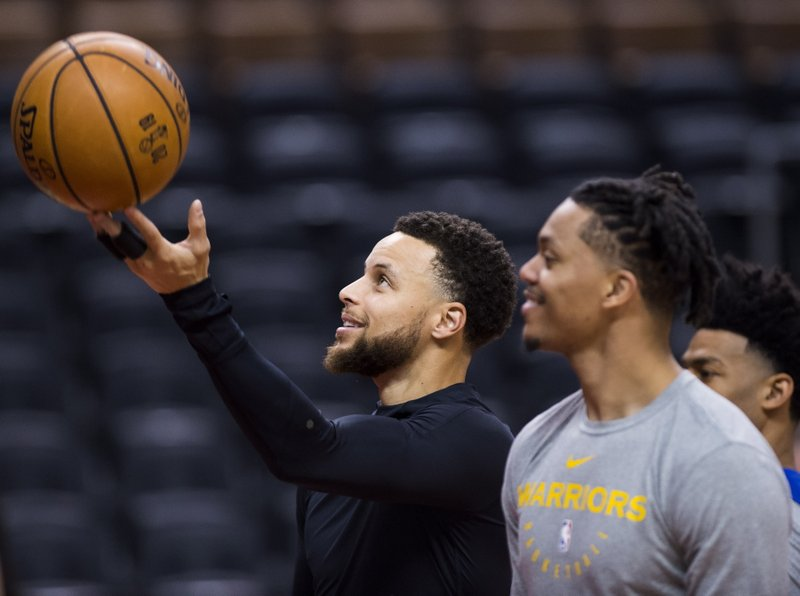 Golden State Warriors basketball guard Stephen Curry, left, shoots during practice for the NBA Finals against the Toronto Raptors in Toronto, Wednesday, May 29, 2019. Game 1 of the NBA Finals is Thursday in Toronto. (Nathan Denette/The Canadian Press via AP)