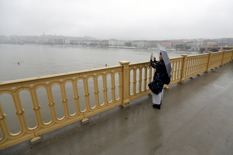 A woman standing takes a picture at Margit Bridge, where the wreck of a sightseeing boat was found on the Danube River, in Budapest, Hungary, Thursday, May 30, 2019. A massive search was underway on the river for missing people after the sightseeing boat with 33 South Korean tourists sank after colliding with another vessel during an evening downpour. (AP Photo/Laszlo Balogh)