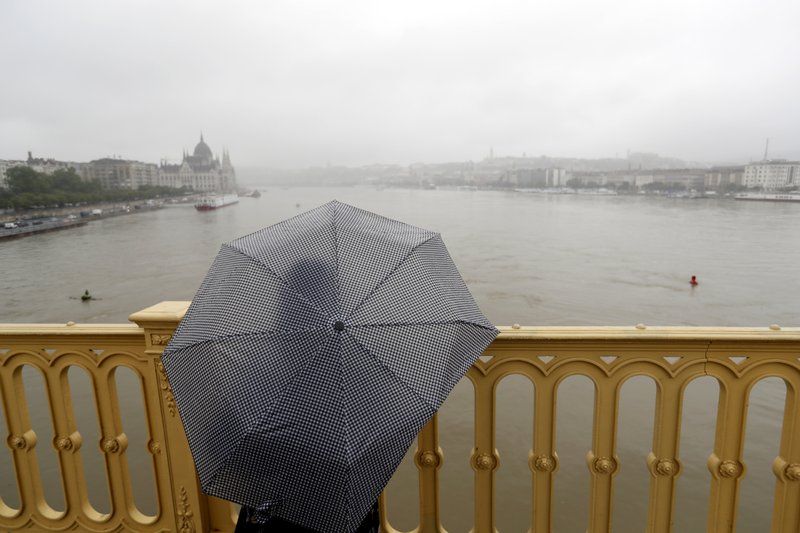 A woman standing looks at Margit Bridge, where the wreck of a sightseeing boat was found on the Danube River, in Budapest, Hungary, Thursday, May 30, 2019. A massive search was underway on the river for missing people after the sightseeing boat with 33 South Korean tourists sank after colliding with another vessel during an evening downpour. (AP Photo/Laszlo Balogh)