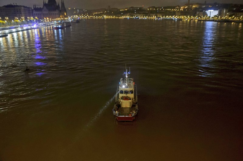 A fire brigade rescue boat takes a part in the search operation for survivors on the River Danube in downtown Budapest, Hungary, Thursday, May 30 2019, as a sightseeing boat collided with another vessel and capsized Wednesday night. The cruise ship sank with thirty-three South Korean passengers and two Hungarian staff on board. (Peter Lakatos/MTI via AP)