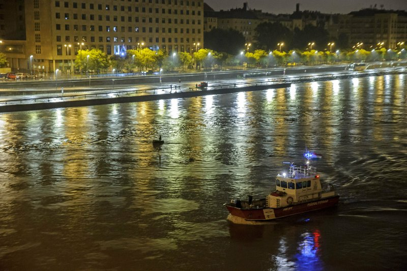 A fire brigade rescue boat takes part in the search operation for survivors on the River Danube in downtown Budapest, Hungary, Thursday, May 30 2019, as a sightseeing boat collided with another vessel and capsized Wednesday night. The cruise ship sank with thirty-three South Korean passengers and two Hungarian staff on board. (Peter Lakatos/MTI via AP)