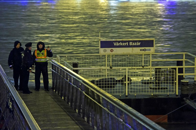 Police officers stand on a landing dock early Thursday, May 30, 2019 after a tourist boat crashed with a river cruise boat in River Danube in Budapest, Hungary, late Wednesday, May 29. The boat capsized and sunk in the river Wednesday evening, with dozens of people on board, including passengers and crew, Hungarian media reported.  (Peter Lakatos/MTI via AP)