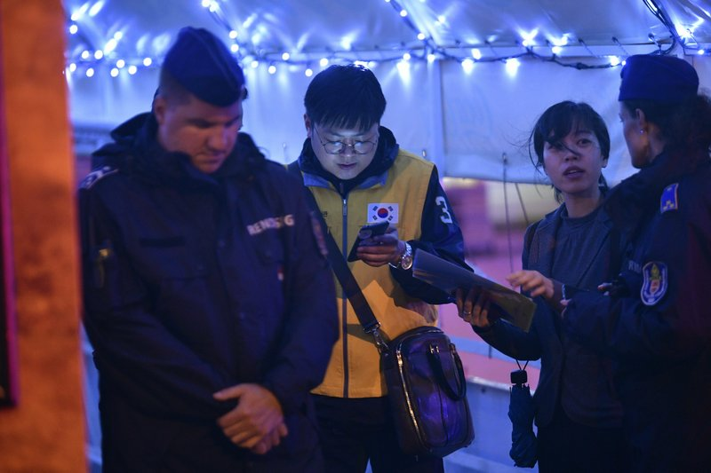Members of the South Korean embassy Budapest staff talk with police officers on the river bank in Budapest early Thursday, May 30, 2019. A sightseeing boat carrying 33 South Korean passengers and two crew members collided with another vessel and sank in the Danube River in downtown Budapest.(Zsolt Szigetvary/MTI via AP)