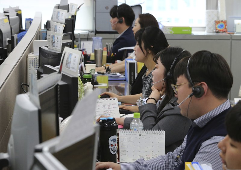 Employees of Very Good Tour Co. talk on the phones at its headquarters in Seoul, South Korea, Thursday, May 30, 2019. A sightseeing boat carrying 33 South Korean passengers and two crew members collided with another vessel and sank in the Danube River in downtown Budapest. The tourists are confirmed to have been on a package tour to Hungary sold by the travel agency. (AP Photo/Ahn Young-joon)