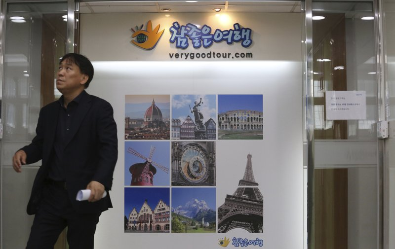 A man stands in front of a gate of the headquarters of Very Good Tour Co. in Seoul, South Korea, Thursday, May 30, 2019.  A sightseeing boat carrying 33 South Korean passengers and two crew members collided with another vessel and sank in the Danube River in downtown Budapest. The South Korean tourists are confirmed to have been on a package tour to Hungary sold by the travel agency. (AP Photo/Ahn Young-joon)