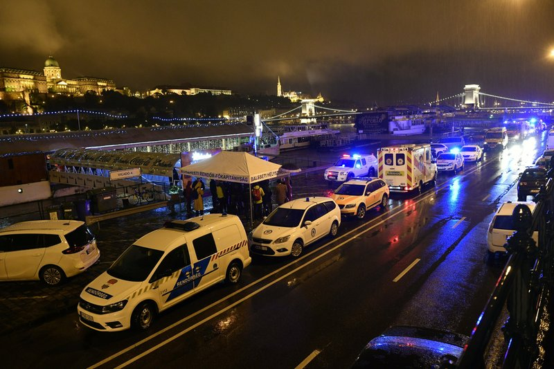 Police and ambulances are parked on the river bank early Thursday, May 30, 2019 after a tourist boat crashed with a river cruise boat in River Danube in Budapest, Hungary. The boat capsized and sunk in the river Wednesday evening, with dozens of people on board, including passengers and crew, Hungarian media reported.(Zsolt Szigetvary/MTI via AP)