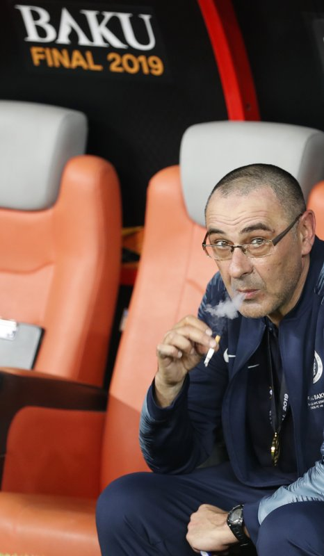 Chelsea head coach Maurizio Sarri smokes a cigaret on the bench after winning the Europa League Final soccer match between Chelsea and Arsenal at the Olympic stadium in Baku, Azerbaijan, Thursday, May 30, 2019. Chelsea won 4-1. (AP Photo/Darko Bandic)