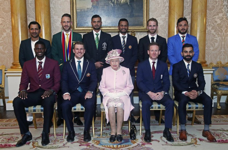 Britain's Queen Elizabeth II joins the captains of the teams taking part in the ICC Cricket World Cup for a photograph in the 1844 Room at Buckingham Palace, before a Royal Garden Party in London, Wednesday, May 29, 2019. Back row from left, Pakistan's Sarfaraz Ahmed, South Africa's Francois du Plessis, Bangladesh's Masrafe Bin Mortaza, Sri Lanka's Dimuth Karunaratne, New Zealand's Kane Williamson and Afghanistan's Gulbadin Naib. Front row from left, West Indies' Jason Holder, Australia's Aaron Finch, England's Eoin Morgan and India's Virat Kohli. (Yui Mok/Pool photo via AP)