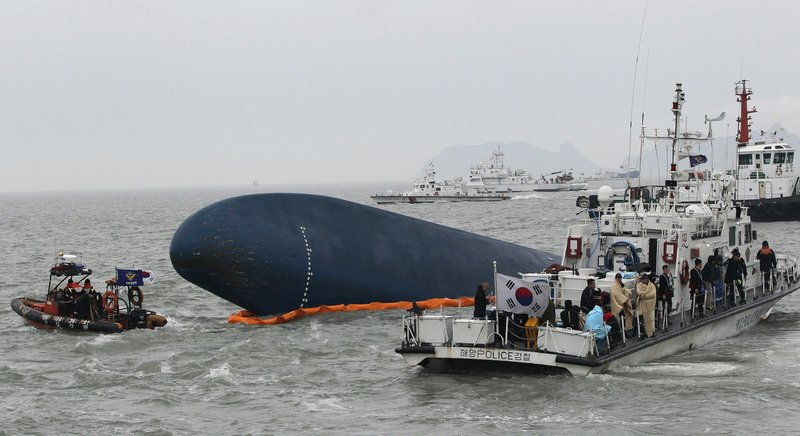FILE - In this April 17, 2014, file photo, South Korean Coast Guard personnel search for missing passengers aboard the sunken South Korean ferry Sewol in the water off Jindo, South Korea. The deadly sinking of a boat in Hungary carrying South Korean tourists on Thursday, May 30, 2019, is touching a nerve in South Korea, where many are still traumatized over a 2014 ferry sinking that killed more than 300 people, mostly school kids. That grief is compounded by some South Korean tour agents and travelers' claims that there have long been worries over safety at the site where the collision happened. (AP Photo/Ahn Young-joon, File)
