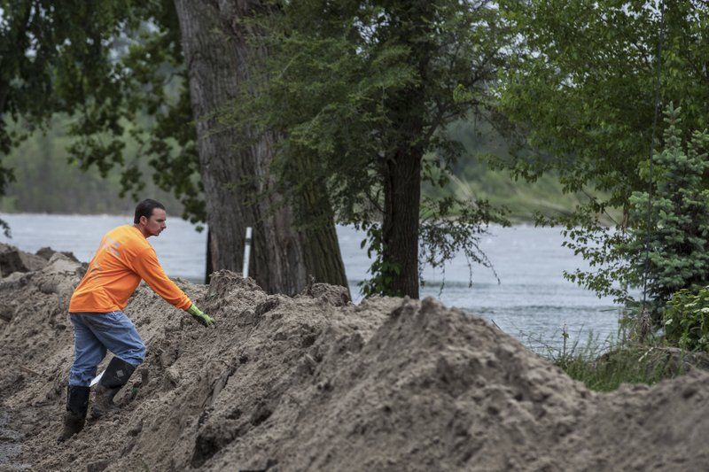 In this Tuesday, May 28, 2019 photo, Josh Tedder inspects rising rising waters from the Platte River as he stands atop a newly built dike at Hansons Lake in Bellevue, Neb. (Chris Machian/Omaha World-Herald via AP)