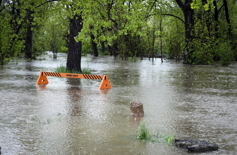 In this Tuesday, May 28, 2019 photo, Rapid Creek overflows its banks covering up a parks department barricade near the Central States Fair Grounds just south of San Francisco Street in Rapid City, S.D. (Adam Fondren/Rapid City Journal via AP)